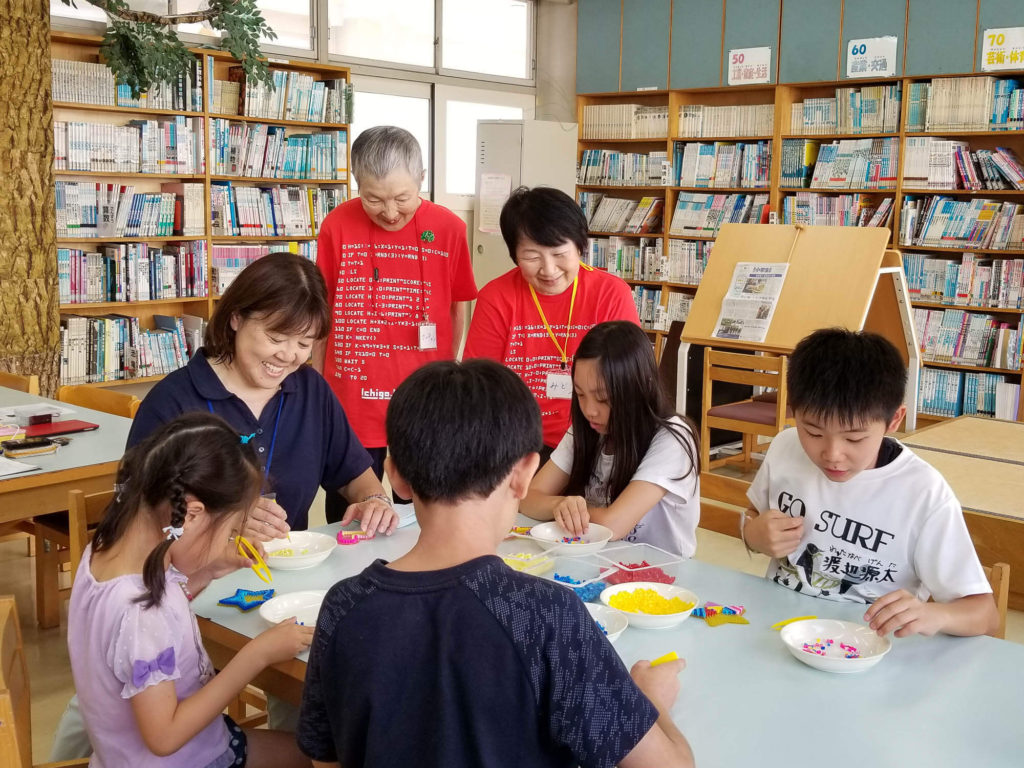 A scene at the Granny's Programing School at Eda Elementary School After-school Kids Club. Four school children are enjoying making stars with fuse beads at the large table with the club instructor, Ms. Inoue, in the school library. Ms. Wakamiya, 83, and Ms. Miyoshi, 62, are in red T-shirts with computer codes, and are smiling at the children.