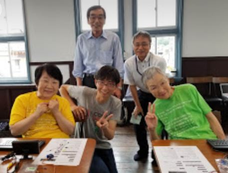 The senior programmers gathered at HANA Dojo in Sabae city at a programing workshop by Mr. Taisuke Fukuno, who developed a computer called Ichigo Jam. Front: Center, the teacher Mr. Fukuno, Left, Ms. Miyoshi, and Right, Ms. Wakamiya. Back: Right, Mr. Makie from the city of Sabae, and Left, Mr. Tanigawa, a programmer.